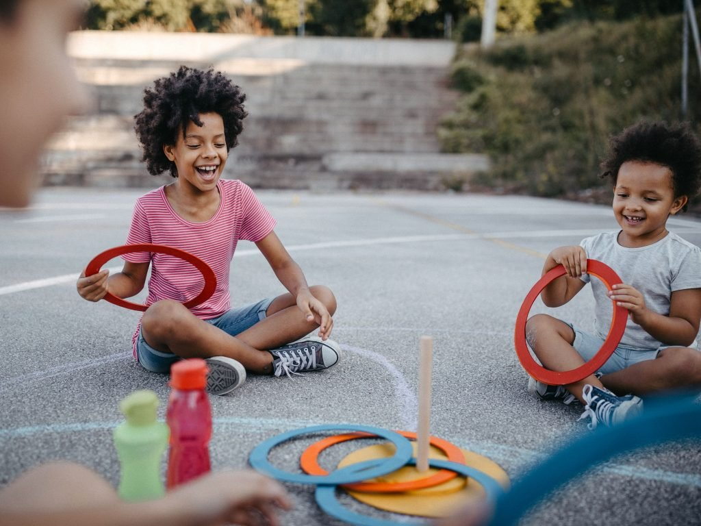 Two young children participating in a ring toss while sitting on pavement. Design a few carnival games for your backyard this summer to keep the kids entertained.