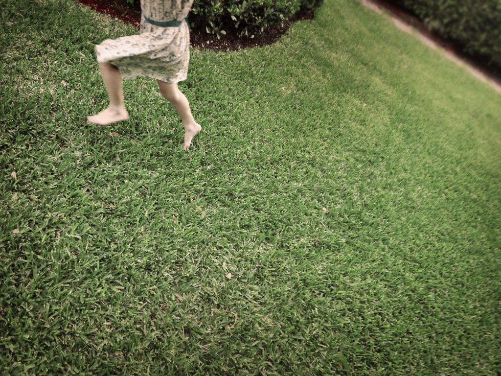 A young girl running in the grass around her house while playing one fo the best backyard games for kids: Annie Annie Over.