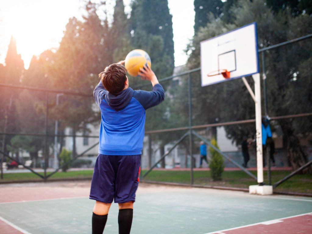 Young boy shooting a basketball into a basketball hoop while playing HORSE, one of the easiest backyard games for kids.