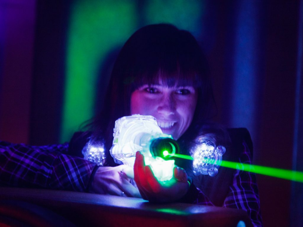 A girl shooting a laser tag gun at her opponent. Laser tag is an easy way to occupy the kids this summer in your backyard
