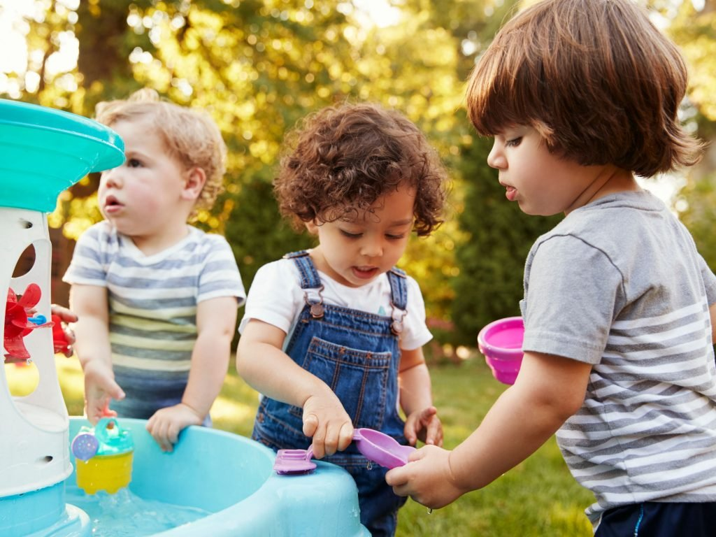 Three Kids Playing With A Water Table. Continue Reading About The Best Water Tables For Kids Below.
