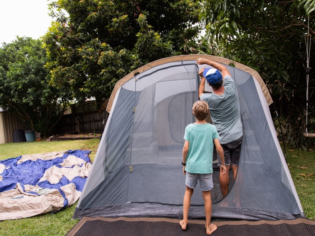 A Father And Son Setting Up A Tent In Their Backyard For Camping.