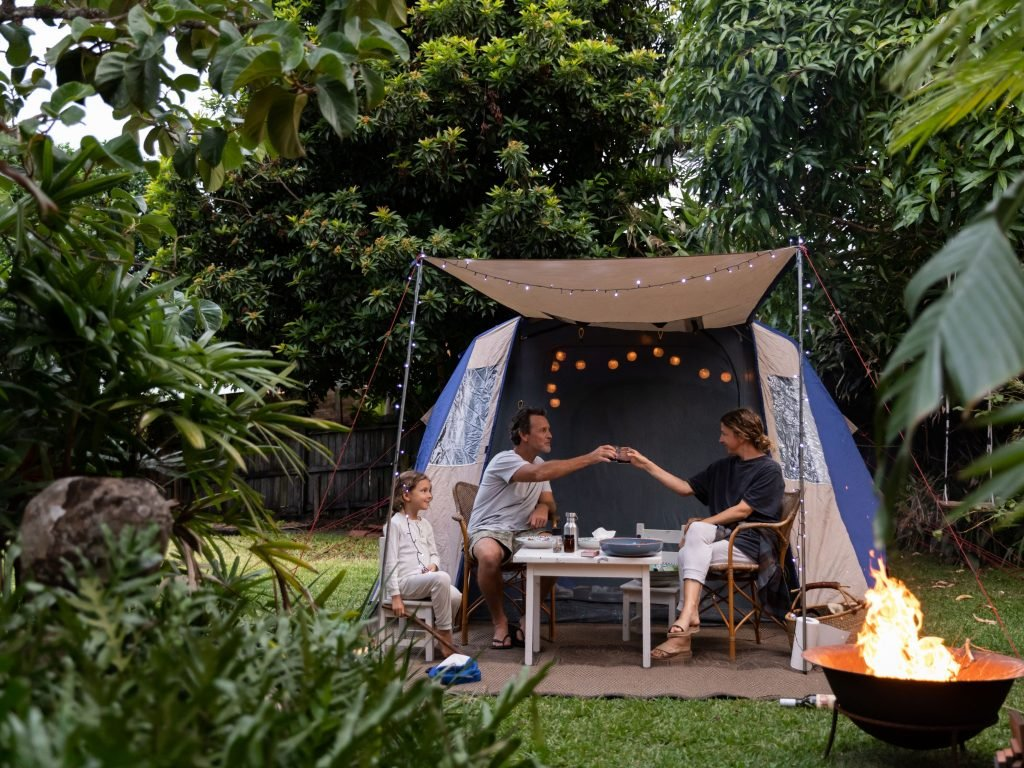 A Family Enjoying A Night Outside In A Tent.