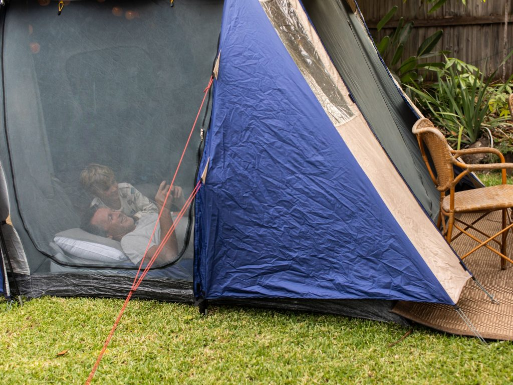 Father And Son Inside A Tent In Their Backyard For Camping.