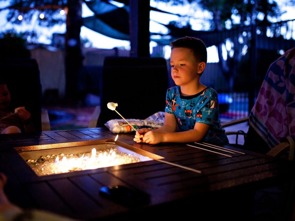 A Boy Roasting A Marshmallow Over A Fire In His Backyard.