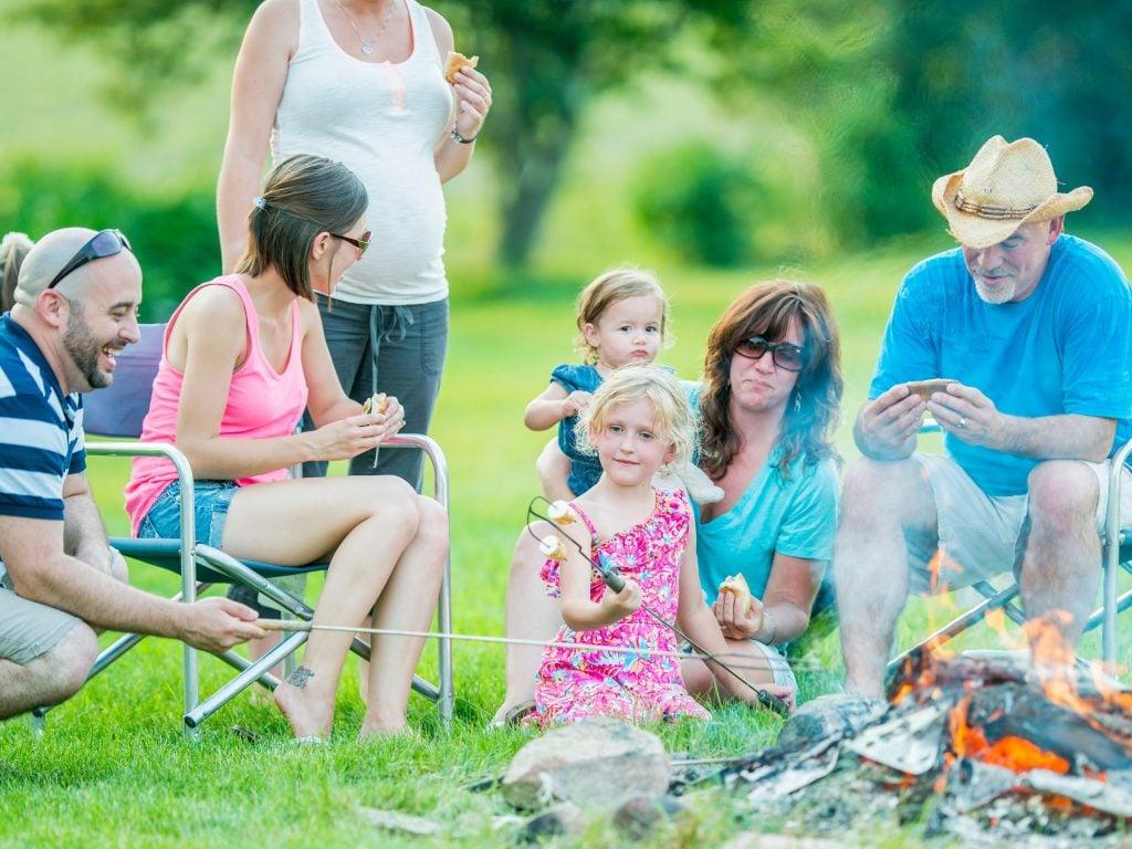 A Family Enjoying S'mores At Their Backyard Camping Night.
