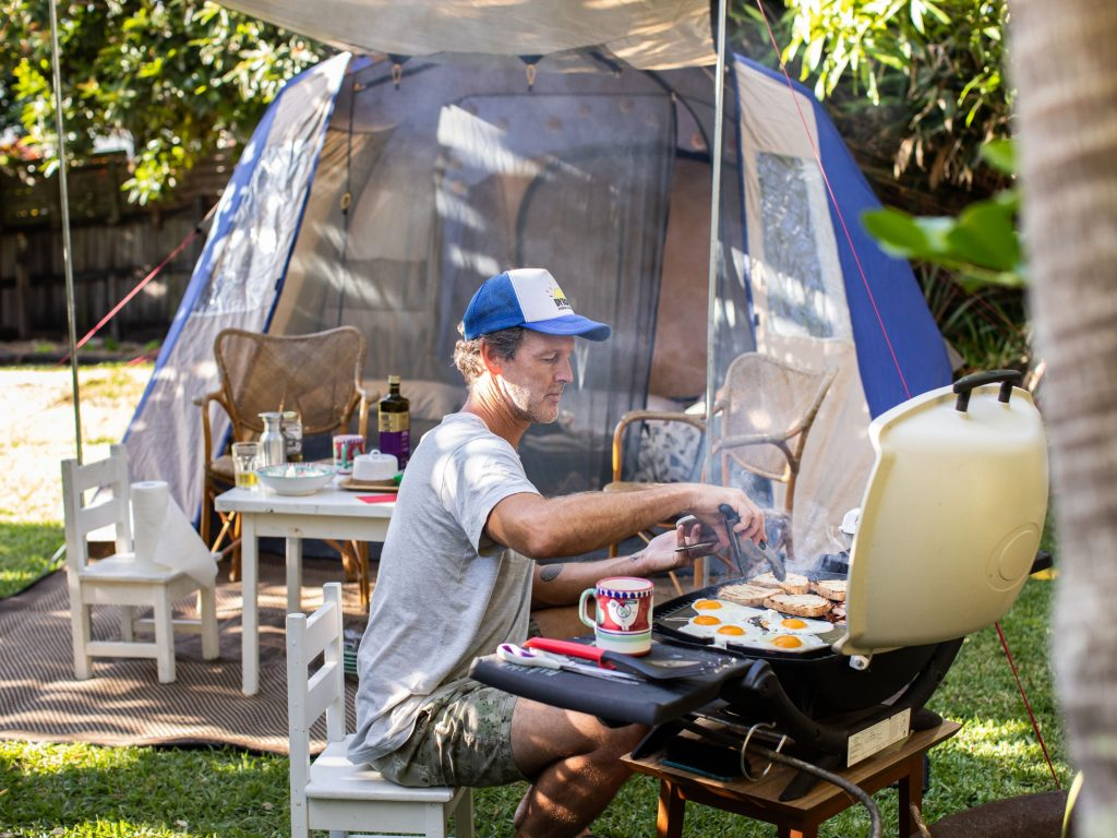 A Dad Using A Camping Stove To Cook Breakfast For His Family. A Camping Stove Is A Staple To Add To Your Backyard Camping Checklist.