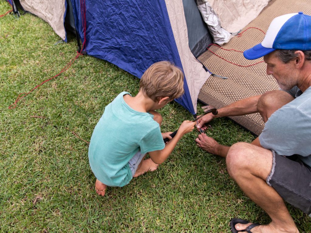 A Dad And His Son Setting Up A Tent In Their Backyard.