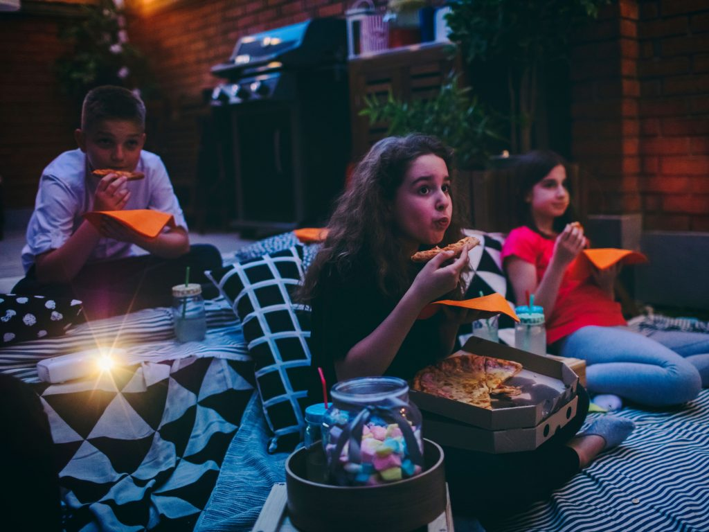 Three Children Sitting On A Blanket Eating Pizza While Watching A Movie Outside.