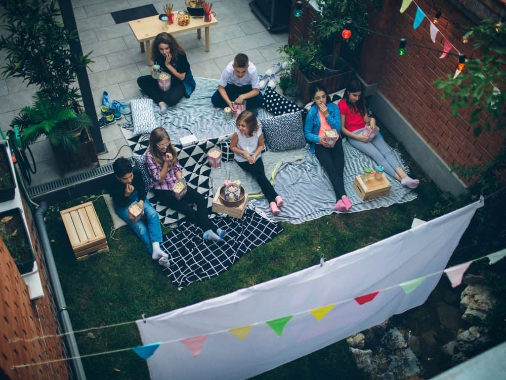 An Overhead View of Children Watching A Movie In A Backyard.