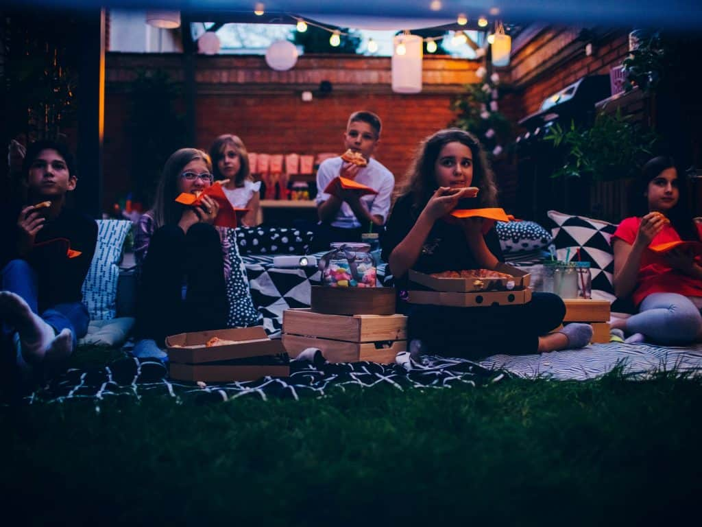 Kids Eating Pizza and Snacks At A Backyard Movie NIght.