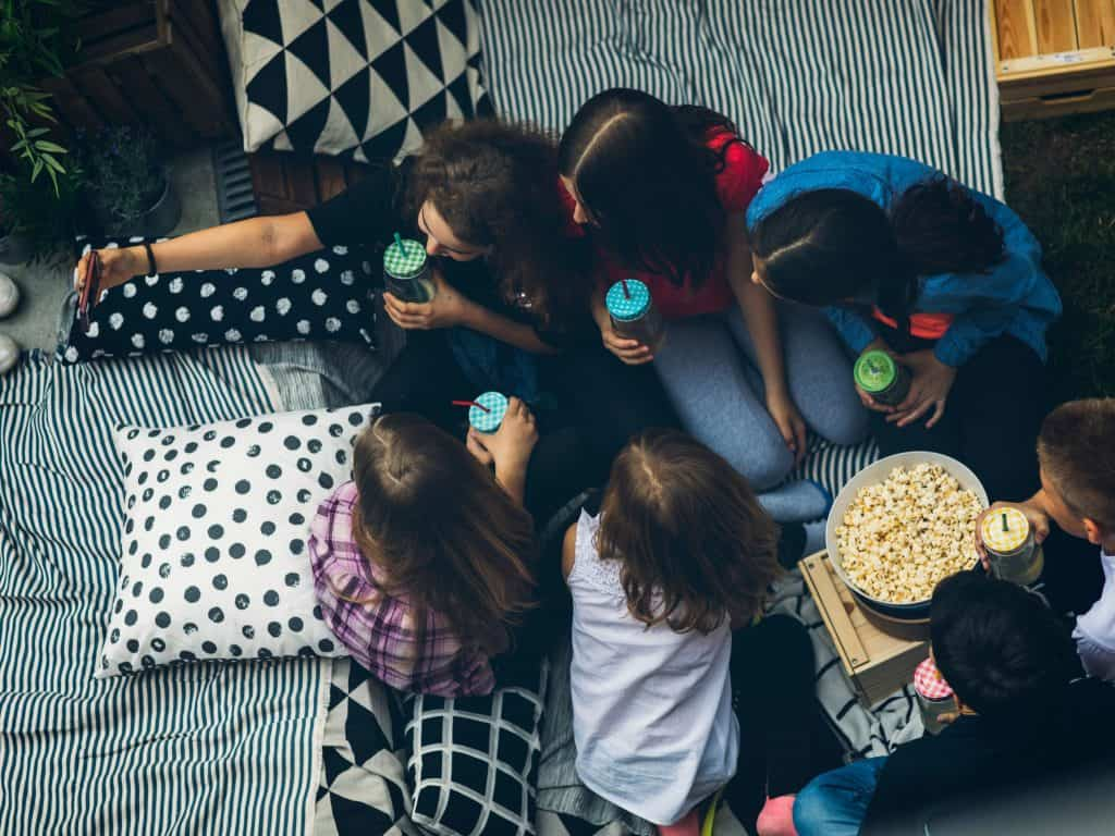 Many Teens Gathered Together With Snacks And Drinks On A Blanket In A Backyard Enjoying A Movie.