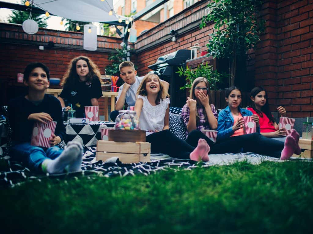 Children Sitting Together On A Blanket In A Backyard For A Movie Night With Snacks.