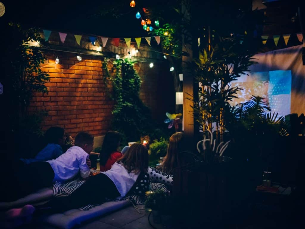 A Backyard Set Up For A Movie Night With Decorations, Lights, And A Movie Screen.