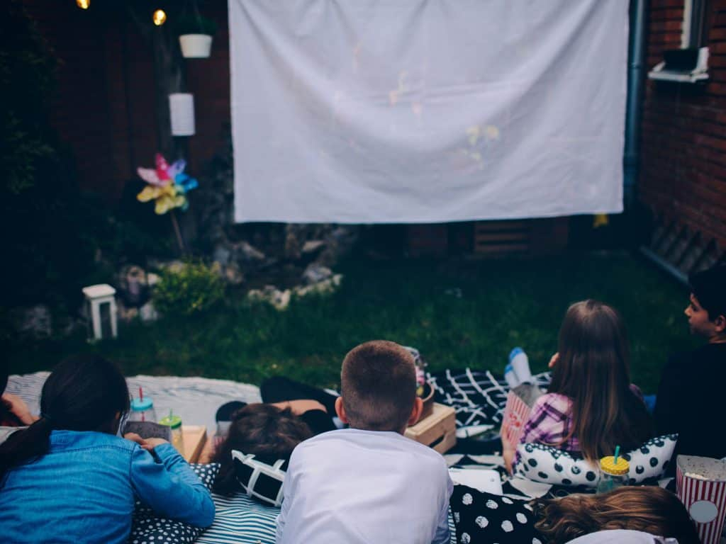 A White Movie Screen Hung Up In A Backyard For Children To Enjoy.
