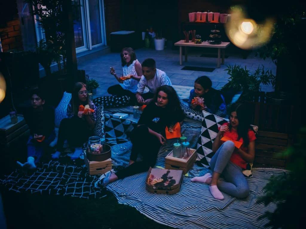 Children Sitting In the Dark Watching A Movie In A Backyard.