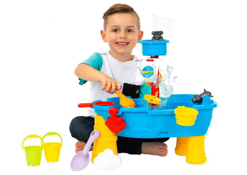 A Small Boy Playing With A Water Table.