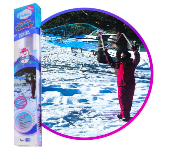 A girl standing in the snow playing with a bubble wand in winter, which is one of the best outdoor winter toys for kids.