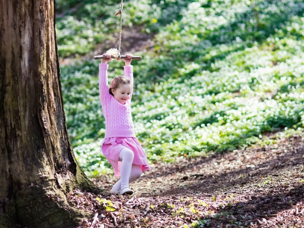 A Young Girl Playing On A Swing In Her Backyard.