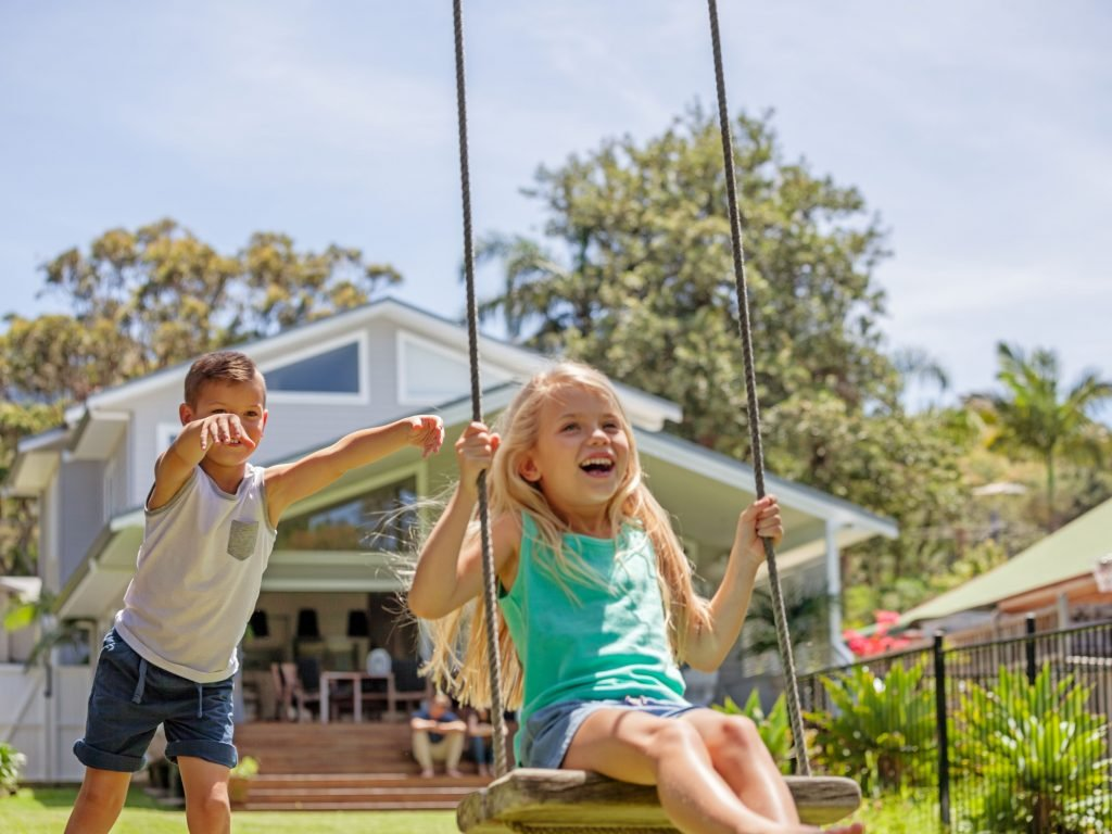 Two Young Girls Laughing And Swinging On A Swing Attached To An Artificial Tree Limb.