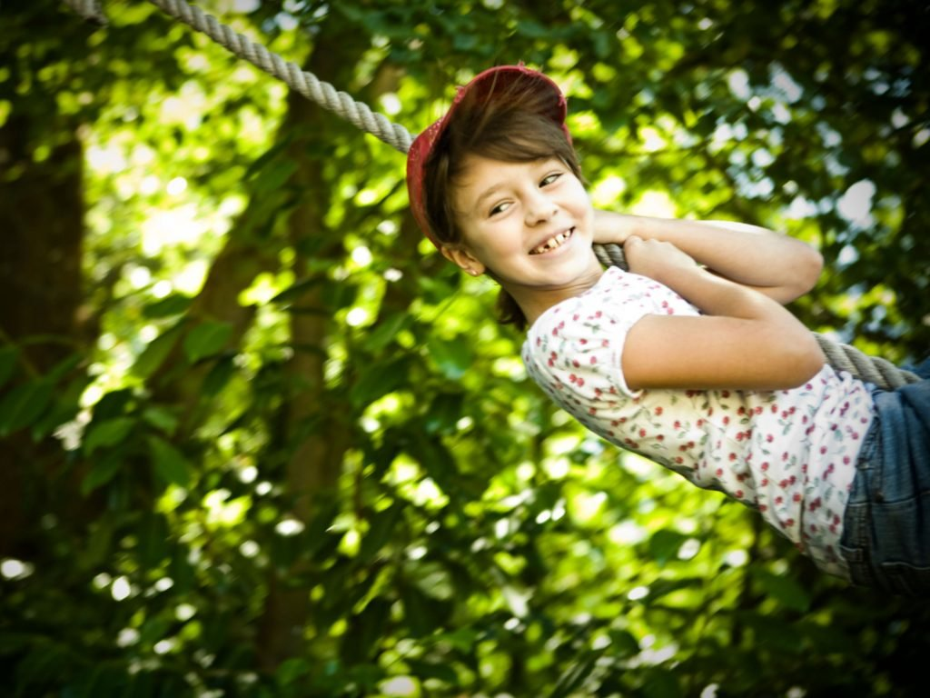 A Young Girl Smiling As She Swings On Her Rope Swing Attached To An Artificial Tree Limb.