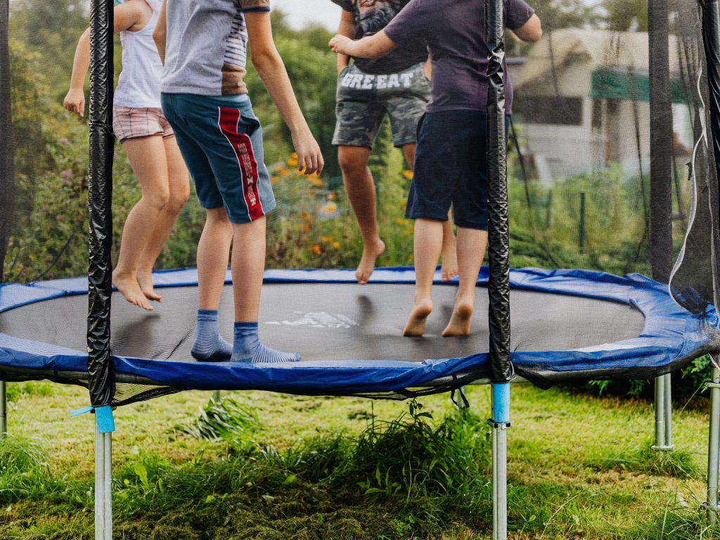Four Older Kids Jumping On A Trampoline.