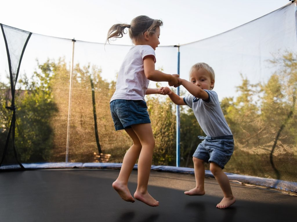 Two Little Kids Jumping On A Trampoline; Adding A Trampoline Tent Will Make It Even More Exciting.