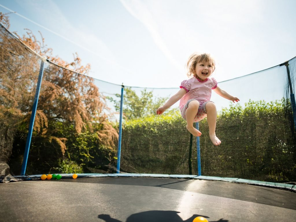Little Girl Jumping On Trampoline.