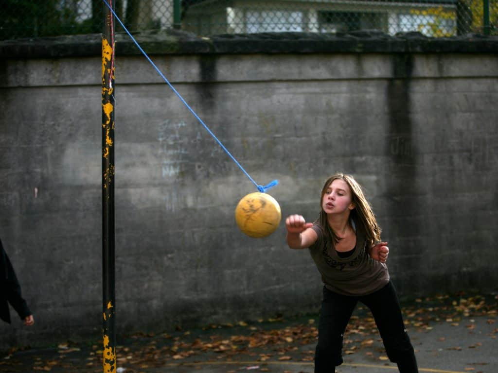 Girl Learning How To Play Tetherball In A School Yard.