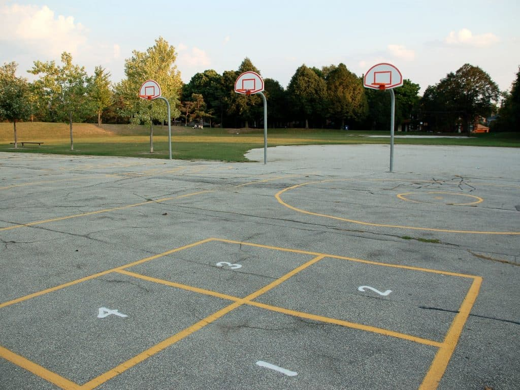 A School Yard With Foursquare Court, Basketball Hoops, and Tetherball Courts.