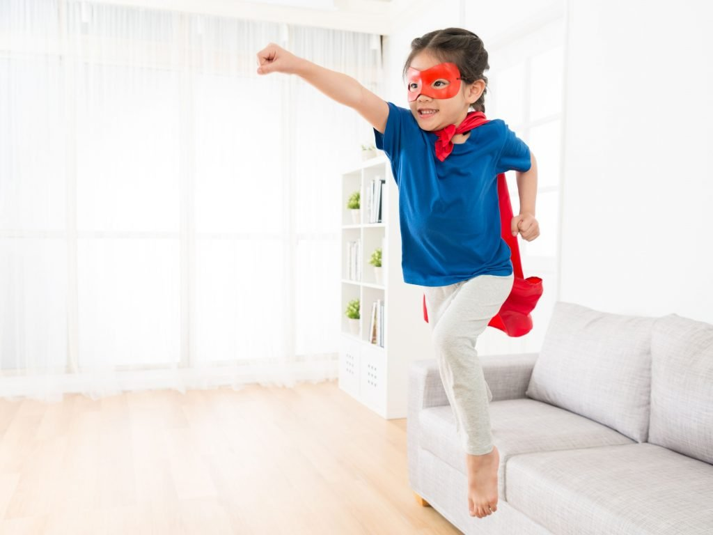Little Boy Jumping From Couch As A Superhero.