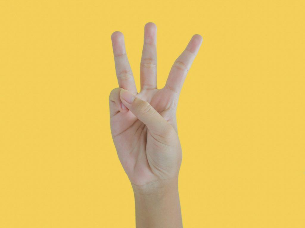 A Hand Holding Up Three Fingers.