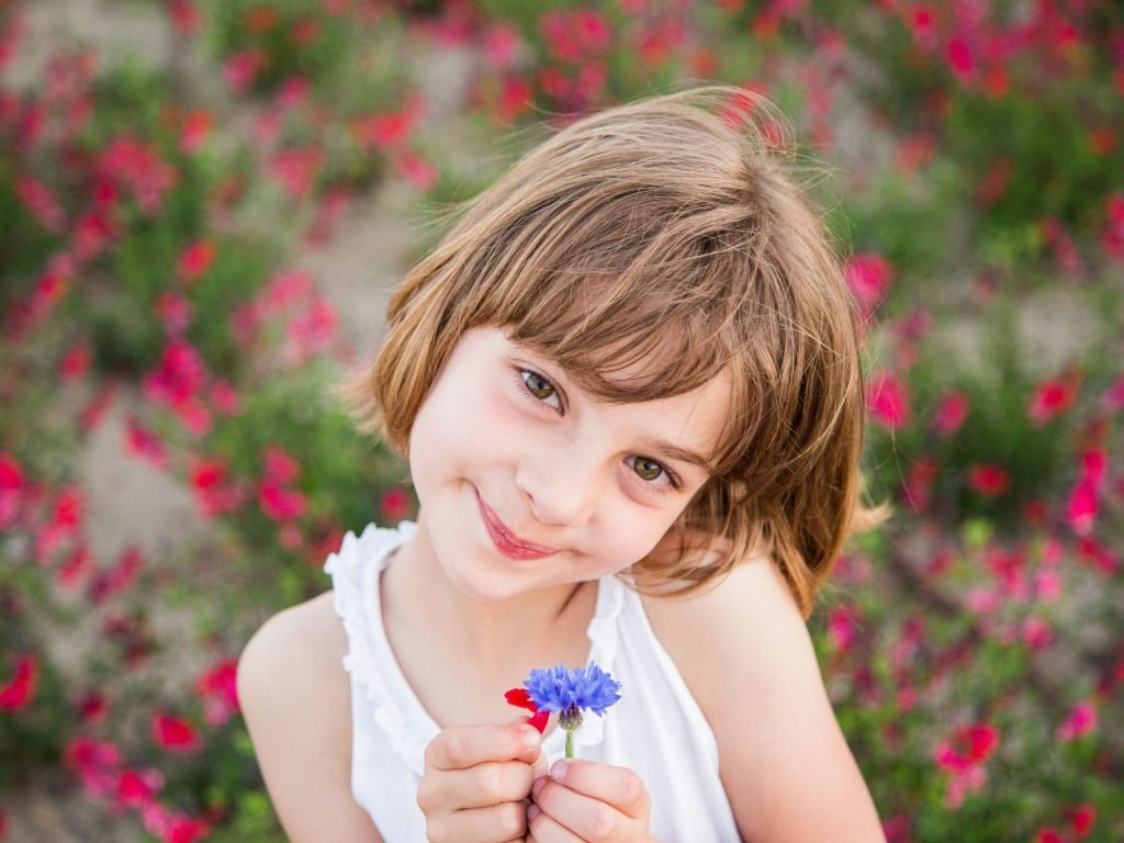 Little Girl Smiling With Flower.