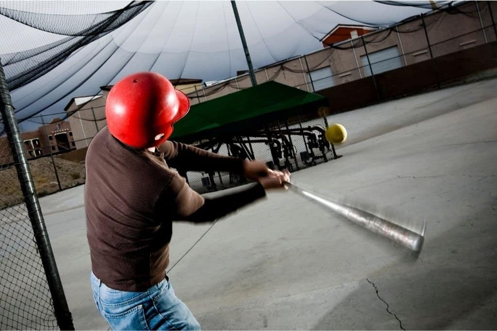 Boy Swinging At A Baseball In The Best Batting Cage.